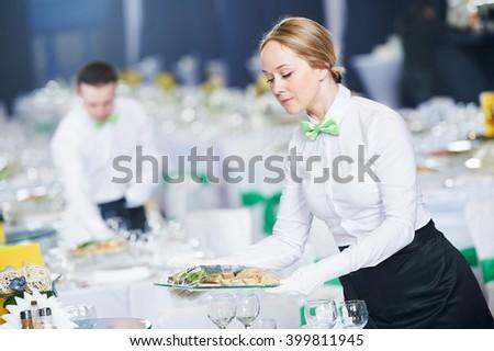 Restaurant services. Female waitress serving table - stock photo