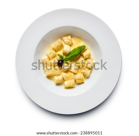 Restaurant shot of perfectly made gnocchi pasta with lots of shredded cheese and creamy sauce decorated with fresh basil and  black olive - stock photo