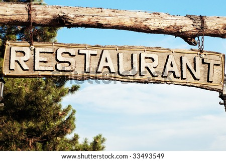Restaurant signboard with carved wooden letters and sky