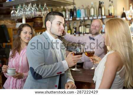 Restaurant smiling visitors waiting for table and drinking wine at tavern. Focus on the man - stock photo