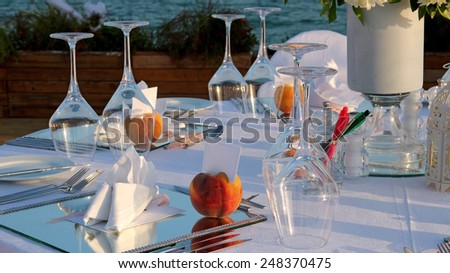 Restaurant Table Setting by the Sea. Fine restaurant dinner table place setting. Table set for an event party or wedding reception. - stock photo