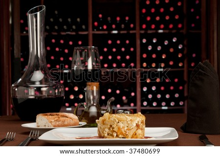 Restaurant table setting with  tapa huevos rotos, literally translated as ?broken eggs?, is a Spanish staple dish of potatoes, ham and eggs. Wine cellar in the background