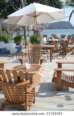 Restaurant table under umbrella overlooking beautiful ocean - stock photo