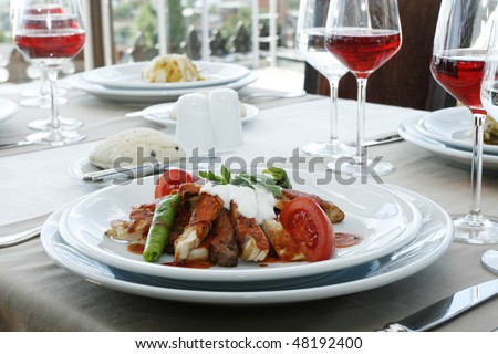 restaurant table with meat and red wine - stock photo