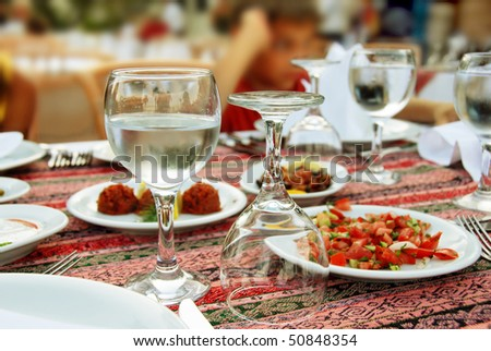 restaurant table with served plate and wine glasses