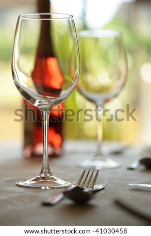 Restaurant table with silverware, wine and wine glasses - stock photo