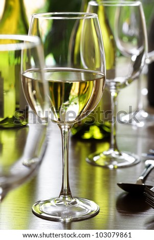 Restaurant table with white wine, silverware and wine glasses - stock photo