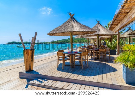 Restaurant tables on beautiful beach in Saint Cyprien coastal town, Corsica island, France - stock photo