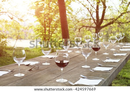 restaurant wine glasses on a wooden table outdoor in the countryside - stock photo