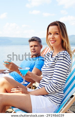Restful dates with cocktails sitting on deckchairs and looking at camera - stock photo