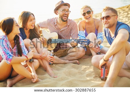Restful friends with drinks sitting on sand by water and singing by guitar - stock photo