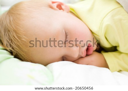 Restful two years baby boy sleeping on bed