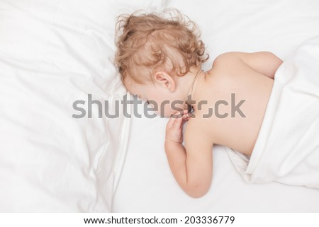 Restful two years old baby girl sleeping on bed - stock photo