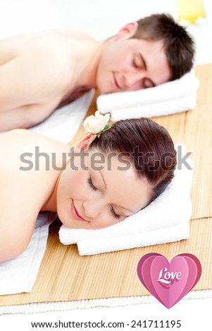 Resting couple lying on a massage table against love heart - stock photo