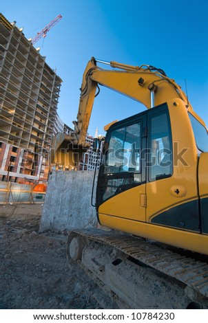resting excavator at the construction place at wide-angle view - stock photo