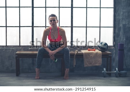 Resting her elbows on her knees, a young, athletic woman is sitting relaxing, resting in between workouts... - stock photo