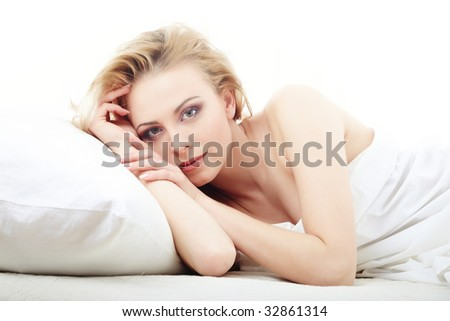 Resting lady laying on the bed on a white background - stock photo