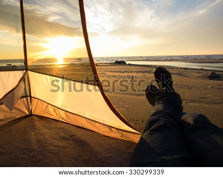 Resting on sea after hiking all day, close up legs. Focused on sea. Natural sunlight. - stock photo