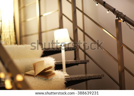 Resting-place with electric garland, book and lamps on modern stairs - stock photo