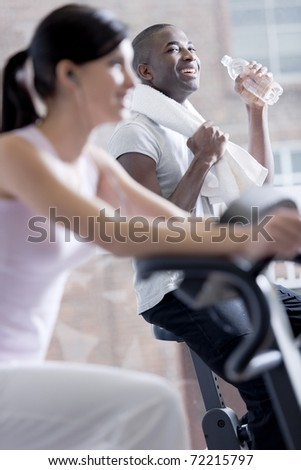 Resting while biking at health club, focus on background - stock photo