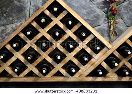 Resting wine bottles stacked on wooden racks in cellar  - stock photo