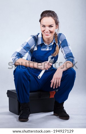 Resting woman sitting on toolbox and holding wrench - stock photo