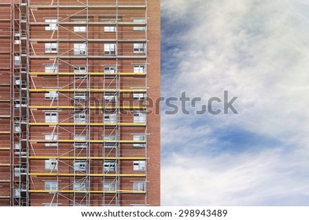 restoration facade of tall house, scaffolding construction, cloudy sky background - stock photo