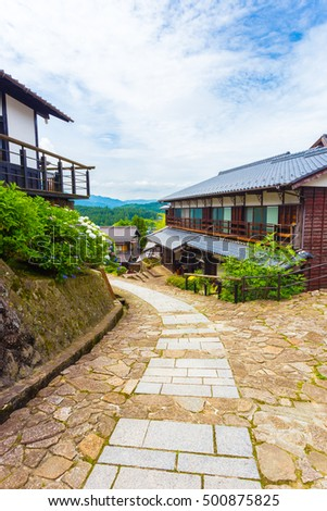 Restored curving stone path leads to traditional wooden houses on the ancient Nakasendo trail on a beautiful blue sky day in Magome, Kiso Valley, Japan