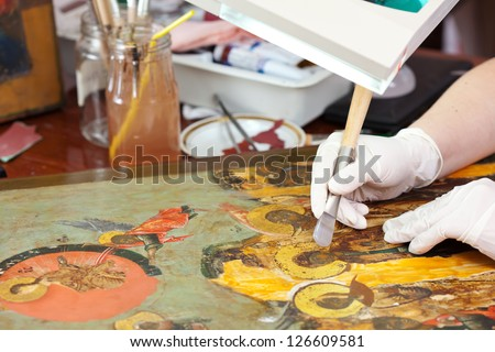 Restorer gilding on the Christian icon with agate burnisher at restoration workshop - stock photo