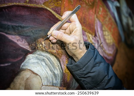 Restorer uses a scalpel to remove pictorial imperfection on a painting surface. - stock photo