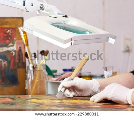 Restorer working on the ancient Christian icon with agate burnisher at restoration workshop - stock photo