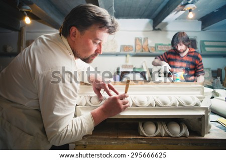 restorers working with gypsum models at workshop - stock photo