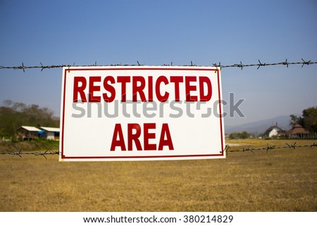 Restricted area sign, red words on white background, barbed wire