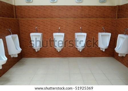 restroom interior photo with urinal row - stock photo