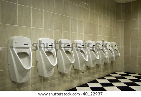 restroom interior with urinal row - stock photo