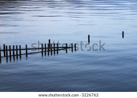 rests of old wooden pier/ jetty sticking out of calm loch Lomond at sunset