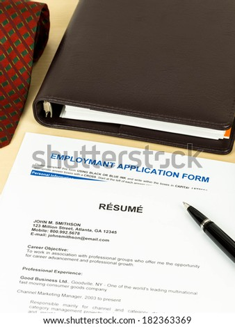 Resume with employment application form, pen, neck tie, and notebook - stock photo