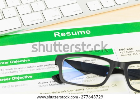 Resume with keyboard and glasses; document and information are mock-up - stock photo