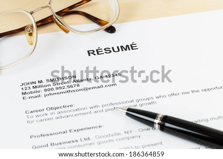 Resume with pen and glasses on table closeup - stock photo