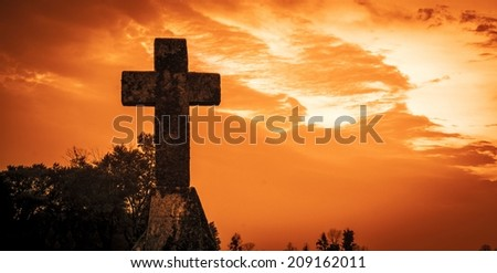 Resurrection. Stone cross against a red sky background.   - stock photo