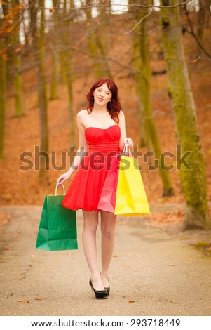 Retail and sale concept. Elegant autumn shopper woman with sale bags outdoor in park after shopping.