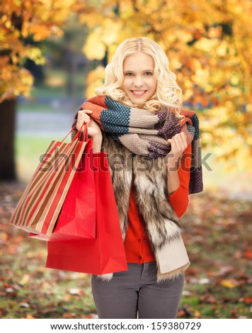 retail and sale concept - happy teenage girl in warm clothes with shopping bags - stock photo