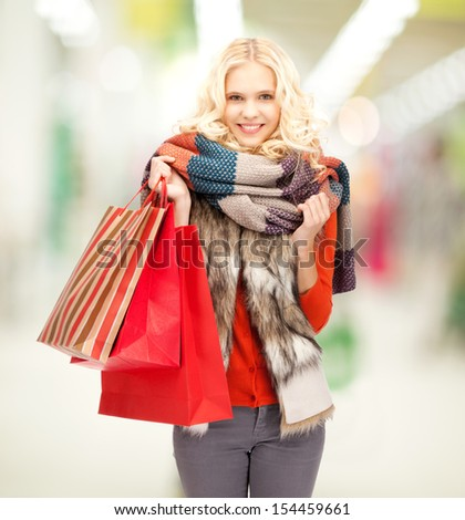 retail and sale concept - happy teenage girl in winter clothes with shopping bags