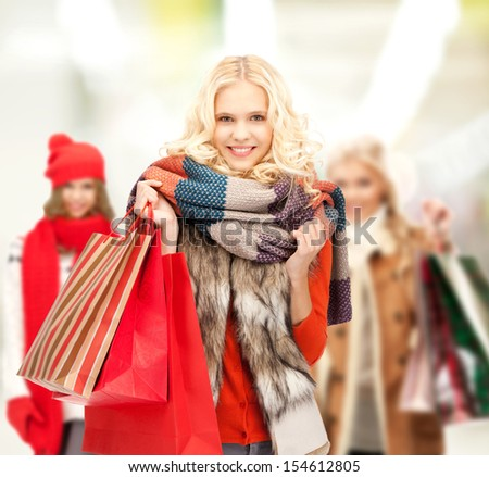 retail and sale concept - happy teenage girls in winter clothes with shopping bags - stock photo