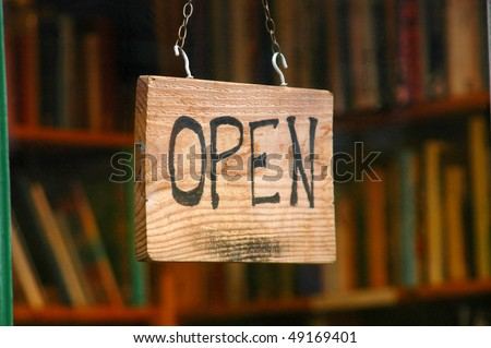 Retail and shopping image of an open sign in a book store window - stock photo