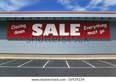 Retail building with a banner on the outside for a closing down sale. Good image for recession concepts. - stock photo