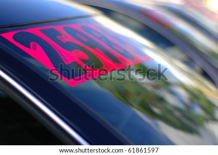 Retail Business Image of Price Stickers on a Row of Used Cars, With Shallow Depth of Focus - stock photo