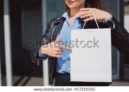 retail concept. Female hand pointing at a blank and white shopping bag. On paper bag space for text - stock photo