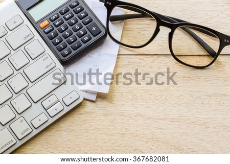 retail online shopping cart icon button on a keyboard, calculator and receipt on table - stock photo