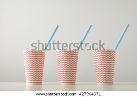 Retail set of three paper cups decorated with red line pattern and with blue drinking straw inside isolated on white table Place for your text above - stock photo